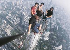 四小伙徒手爬大厦顶塔尖拍照 律师:涉嫌扰乱公共秩序